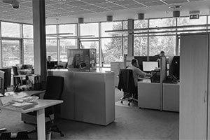 Biuro w firmie Can Agri, mężczyzna siedzi przy komputerze, biuro jest przeszklone.